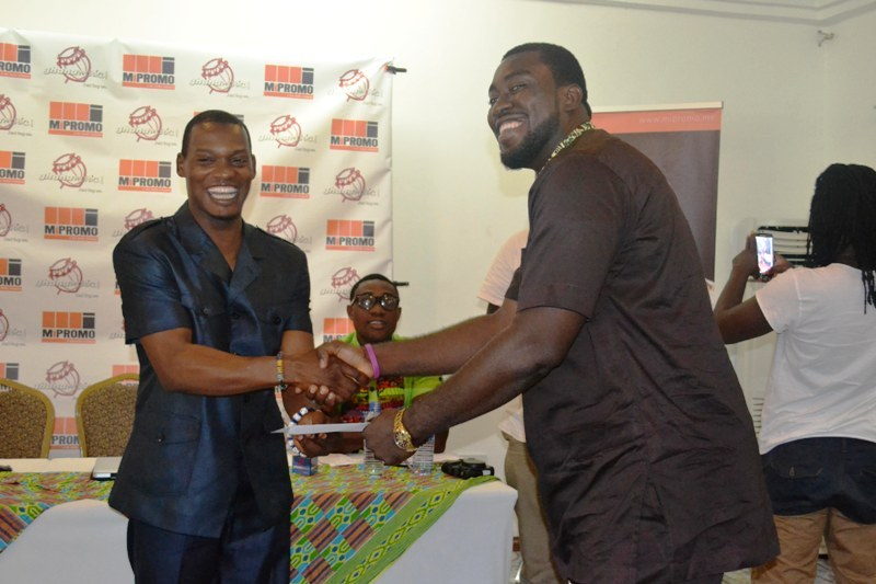 Kwasi Ernest presenting a payment. Photo Credit: MiPRMO